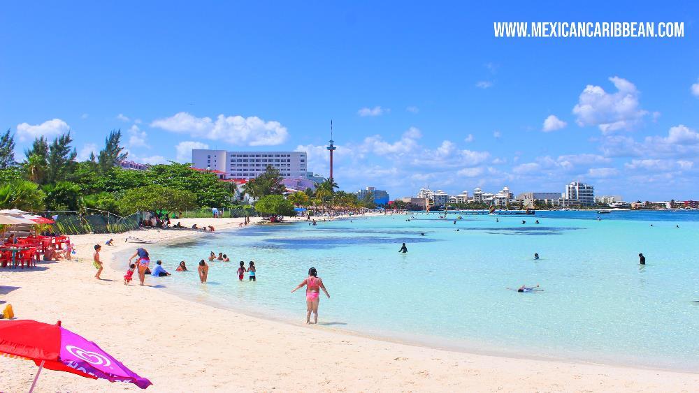 Personas disfrutando de las aguas de playa Tortugas en Cancún